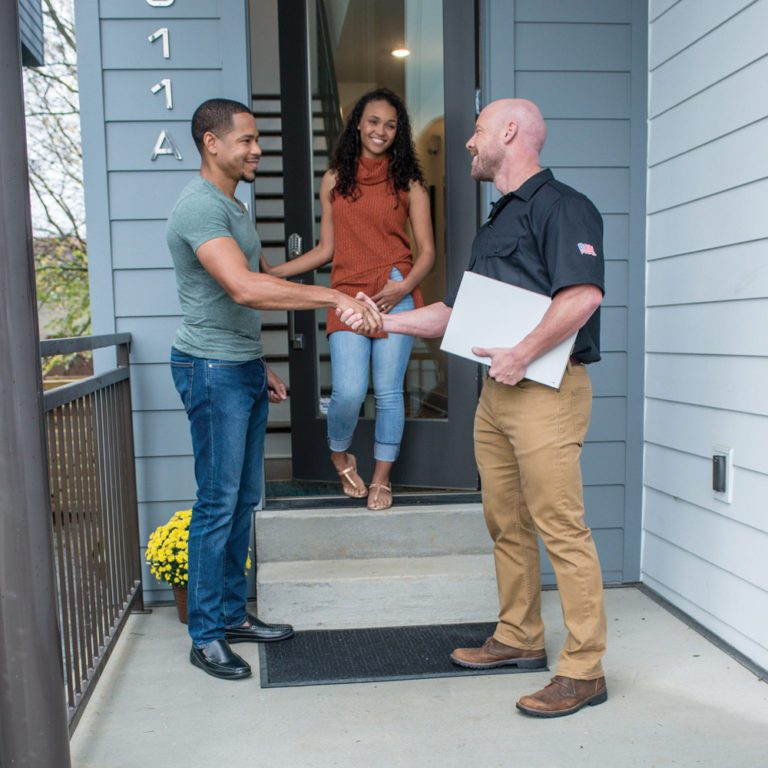Happy customers shaking hands with contractor from their reviews